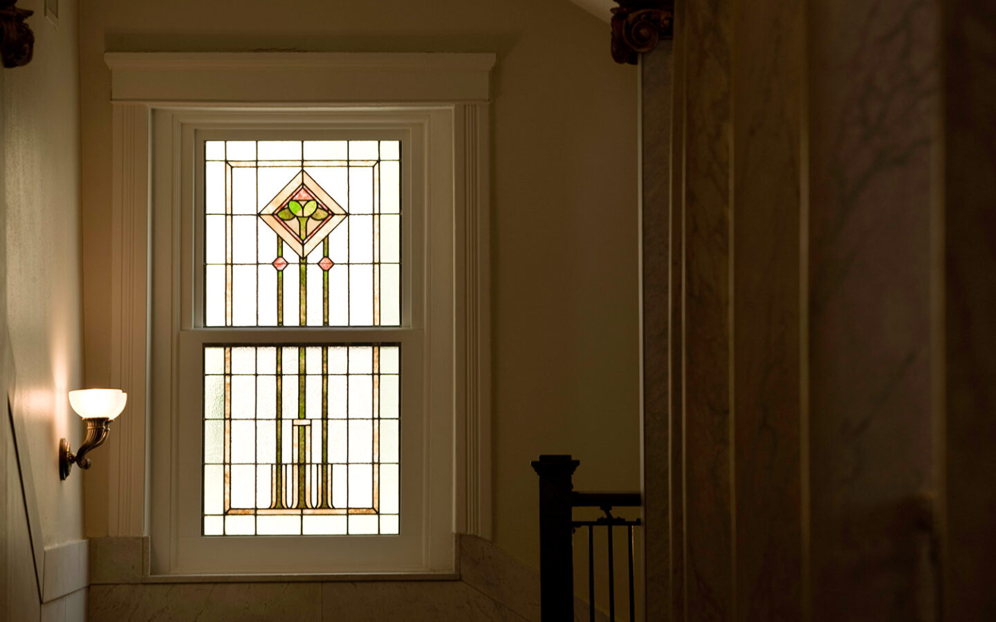 photo of a hallway with a stained glass window at the end