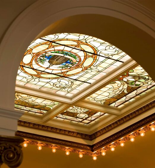closeup of a ceiling behind an arch with a stained glass window