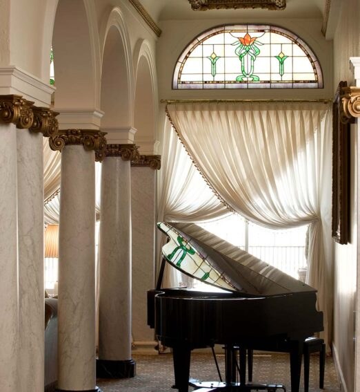grand piano beneath a stained glass window next to large arches and columns in a lobby