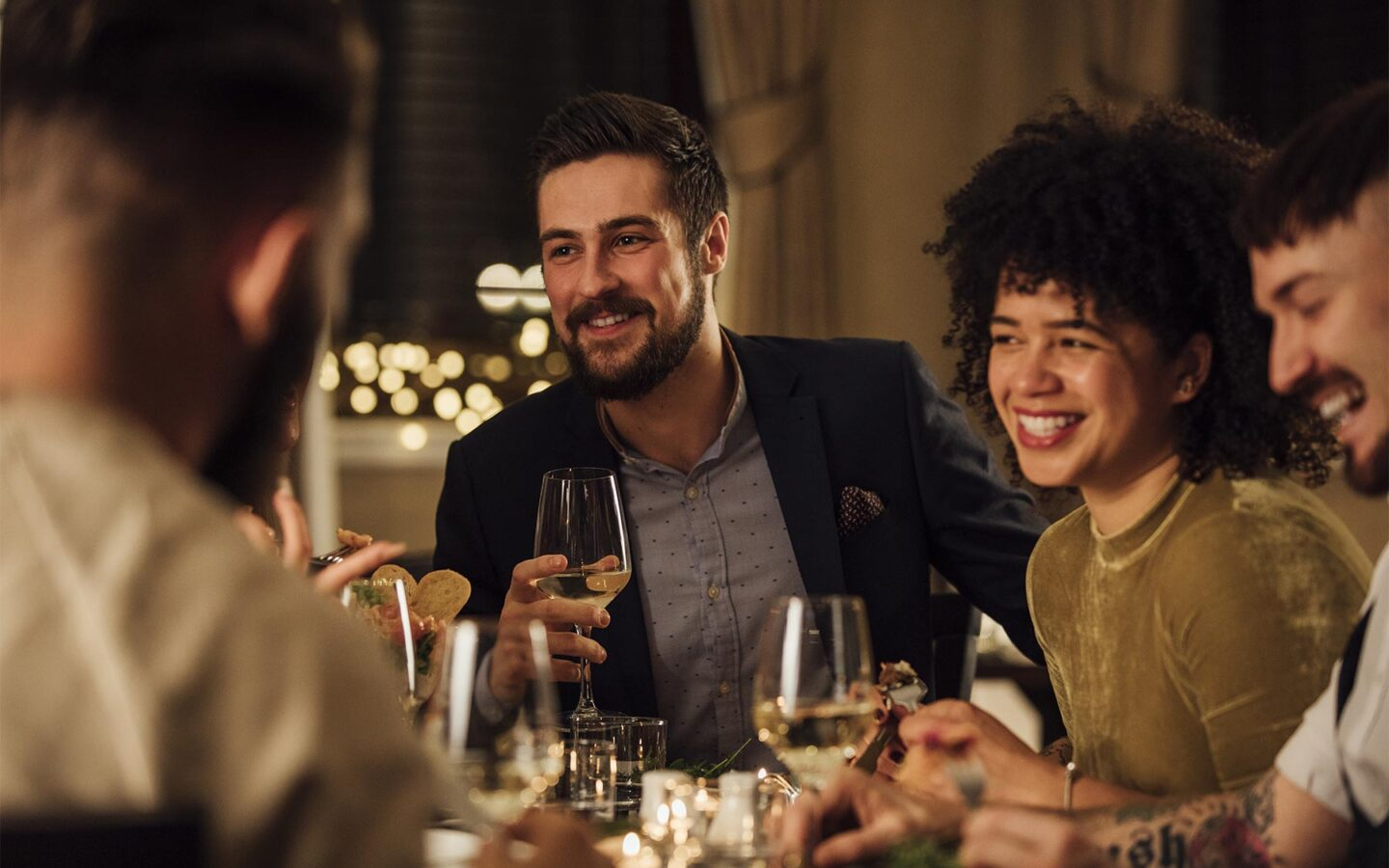 man and woman smiling at a restaurant table with wine glasses in hand
