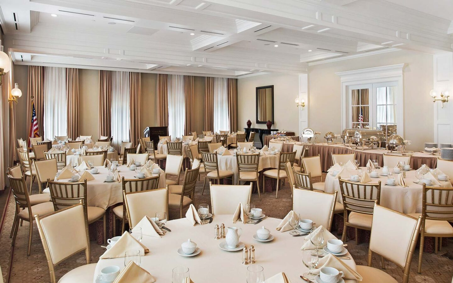 large hotel dining room with round white tables and chairs and a buffet table