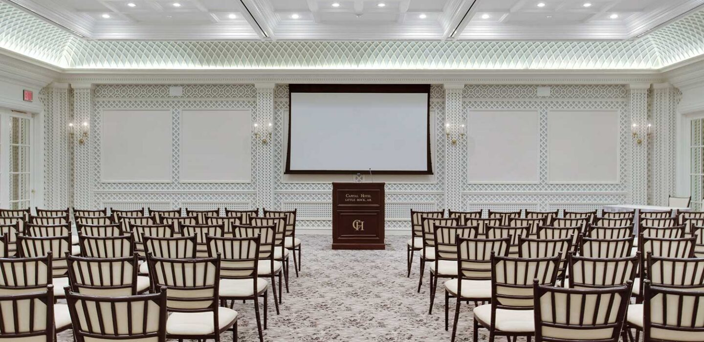 large event venue room lined with chairs and a podium in front of a projector screen