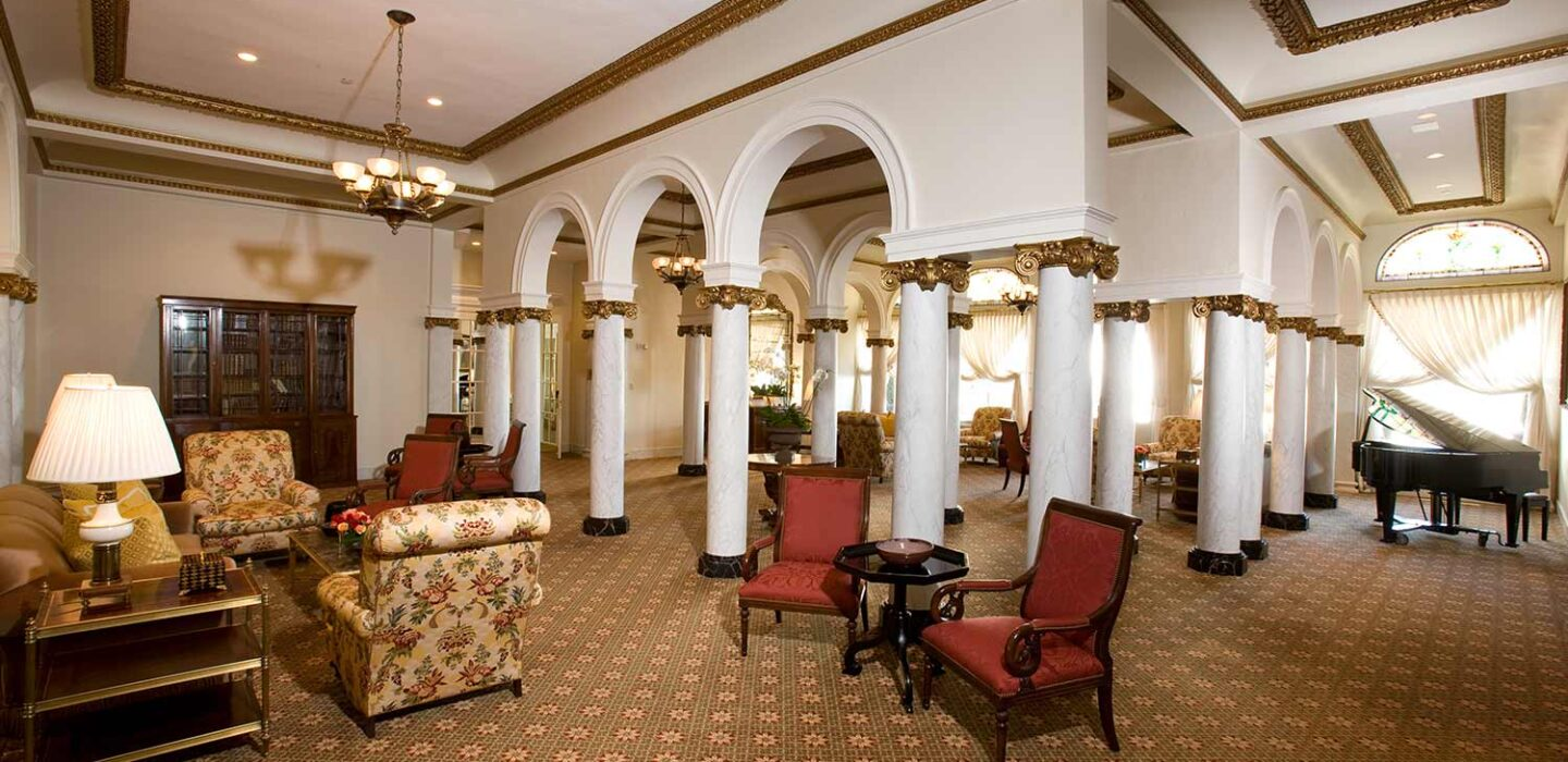 hotel lobby with large arches and columns and vintage style couches