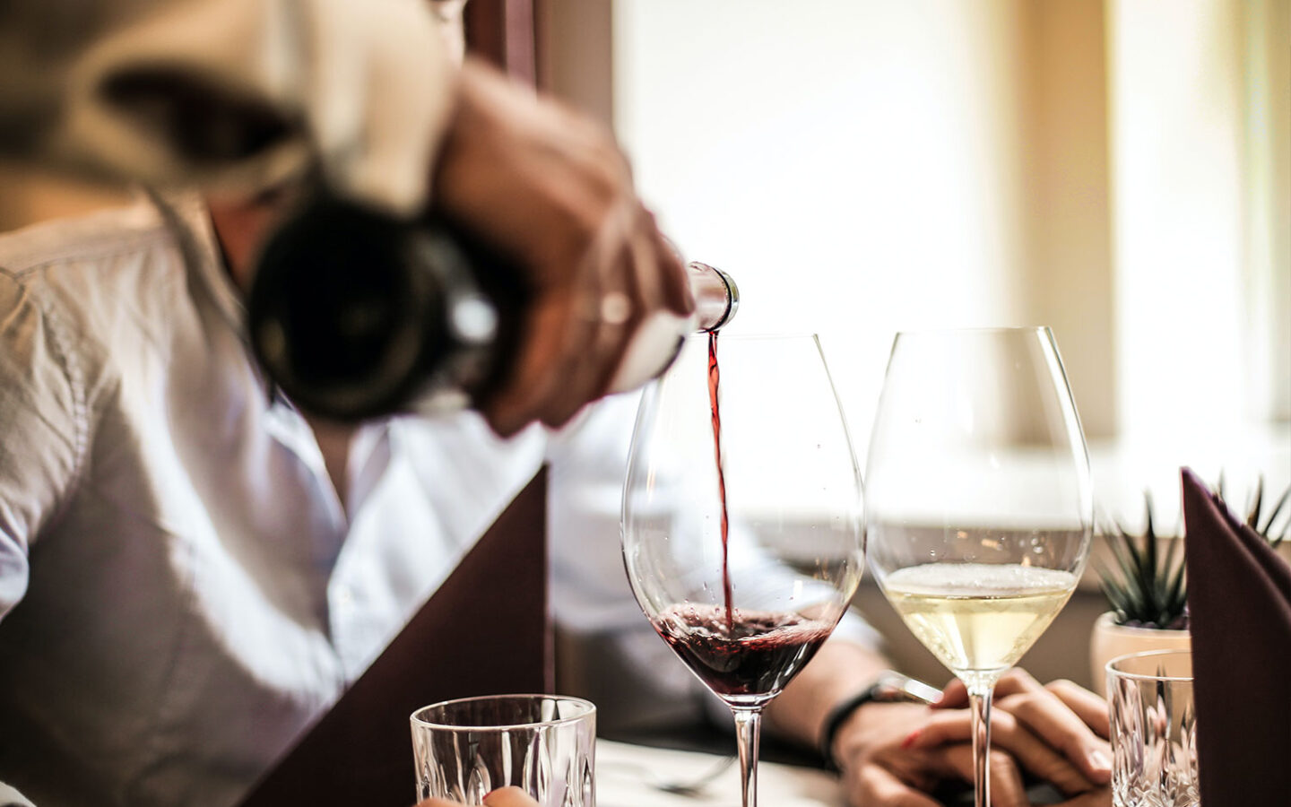 closeup of a waiter pouring red wine into a clear wine glass