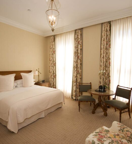 guest room with a king bed, large wooden dresser and a small table area
