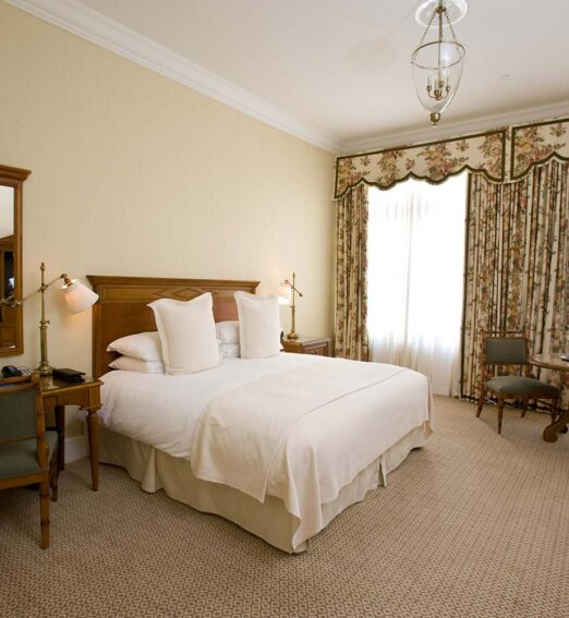 hotel room with a king bed, small round table and chairs, and a small desk and wall mirror