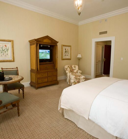 hotel room with a king bed, large wooden tv stand, and a small round table and chairs