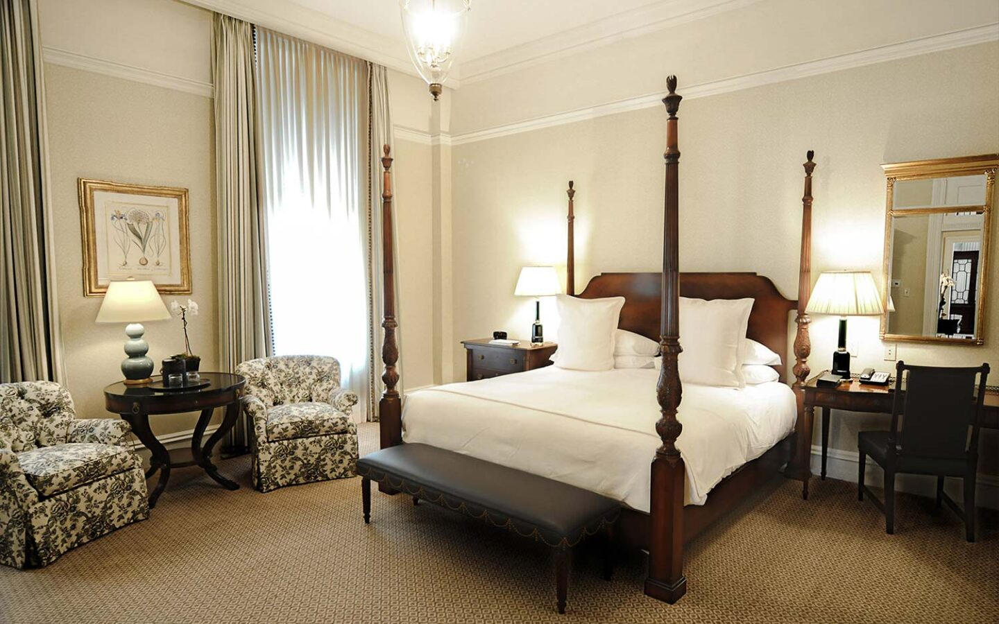king bed with tall wooden bed posts with a desk and mirror and a small seating area