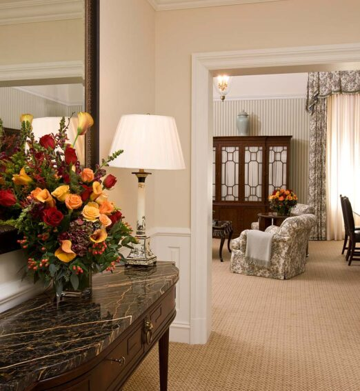 grand capital suite entrance with a marble console table and wall mirror