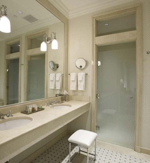 large hotel suite bathroom with a double vanity with a full wall mirror and walk in shower