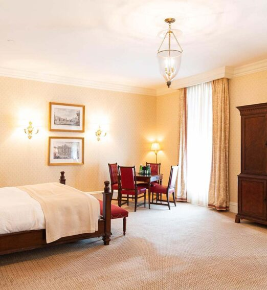 guest room with a large bed, chandelier, seating area, and wooden dresser