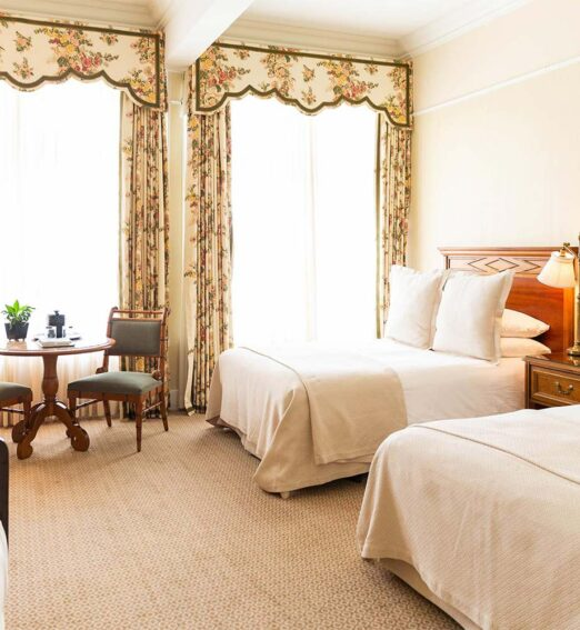 guest room with two double beds, small table, and a large wooden dresser next to two large windows