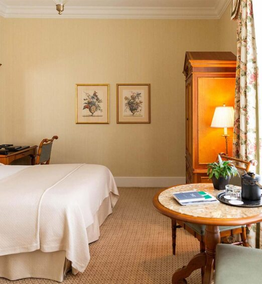 room with a king bed, round table and chairs, wooden desk and mirror, and a large wooden dresser