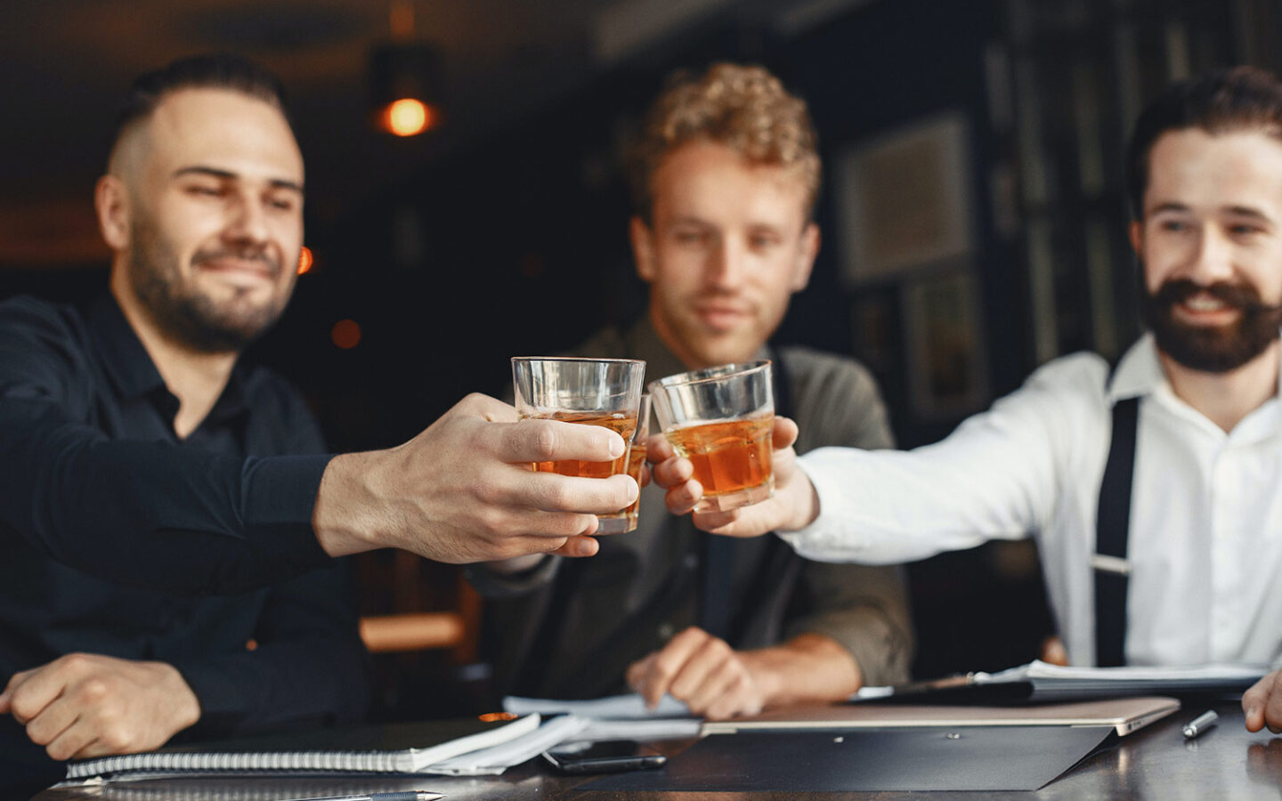 three men sitting at a bar clinking their glasses together