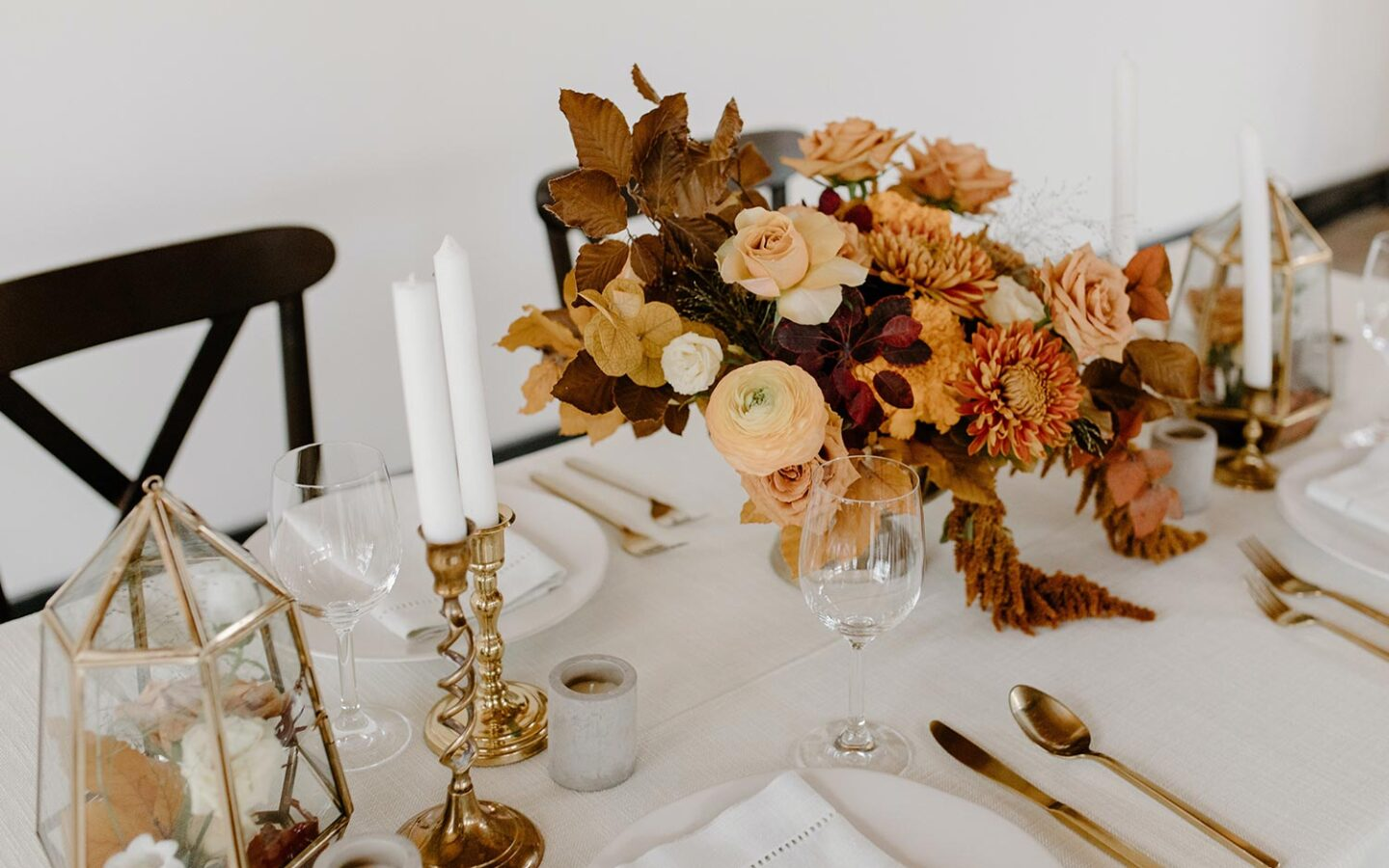 table setting with autumn flowers and gold cutlery