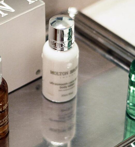 three small bottles of soaps on a silver tray