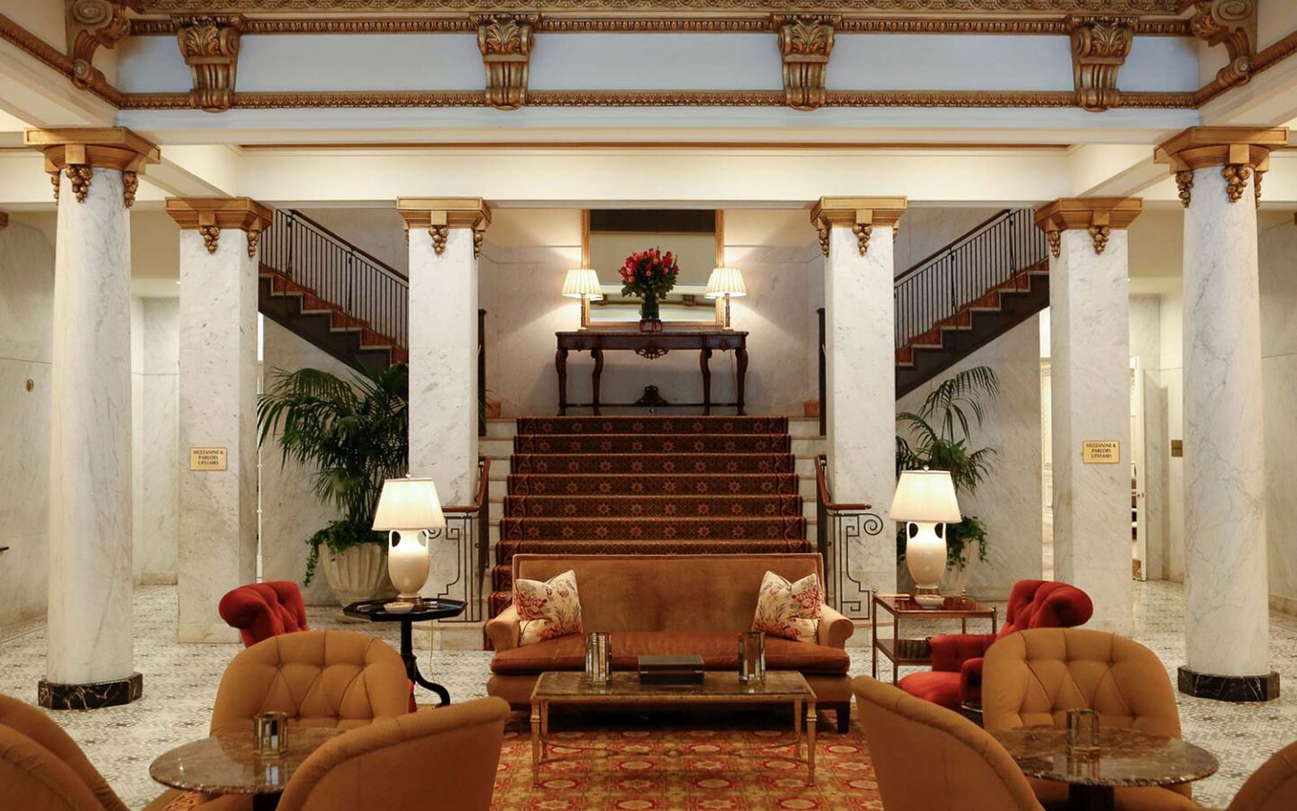 hotel lounge with a grand staircase, large columns, and comfy couches