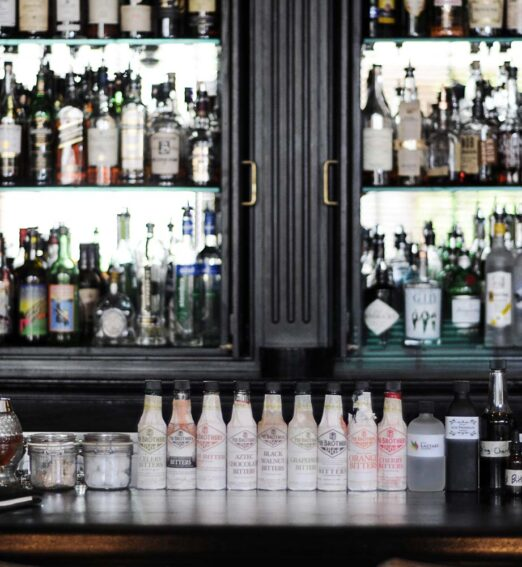 bar with bottles on display behind and on top of it