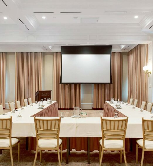 meeting venue with large curtains and a U shaped table in front of a projector screen