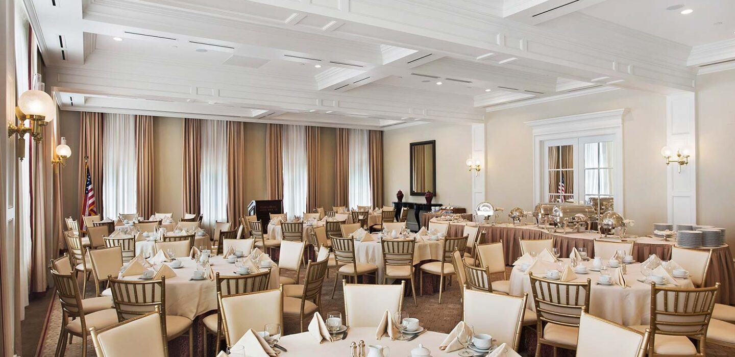 meeting venue with large curtains and many round tables with chairs set up next to a food table