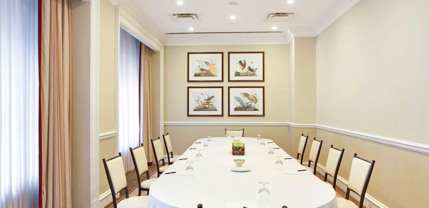 meeting room with a large oval table with chairs and large windows