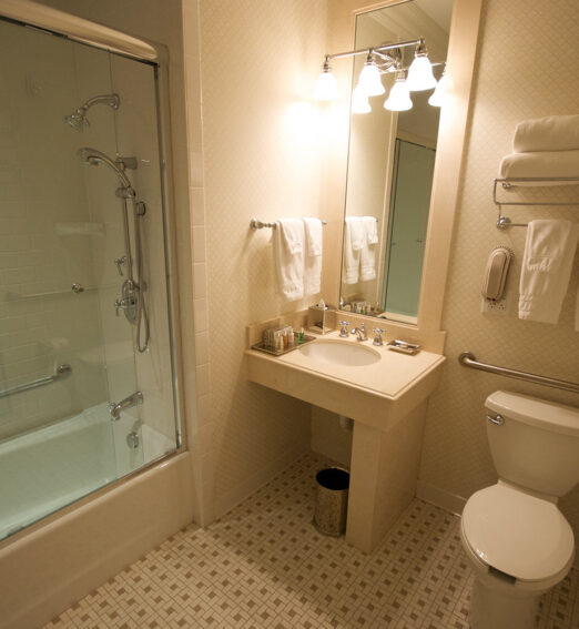 bathroom with a bathtub, single vanity, and individual toilet