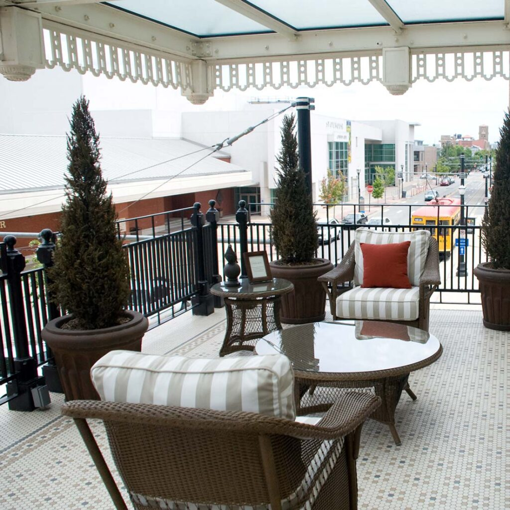 balcony patio with outdoor couches and potted trees