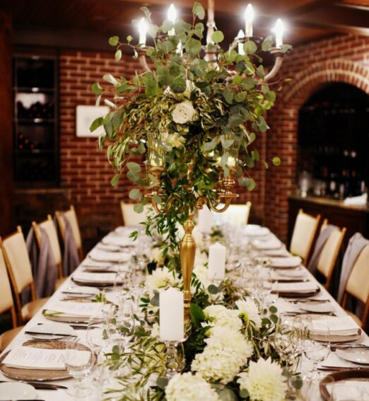 long event table set with white linens and large floral centerpiece