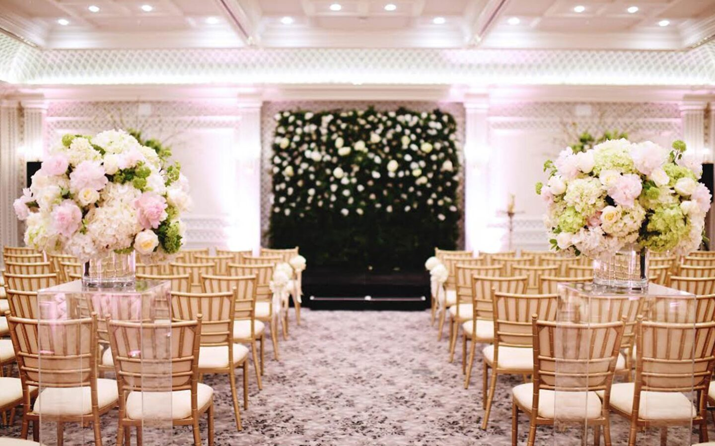 wedding venue with rows of gold chairs leading to large floral arrangements
